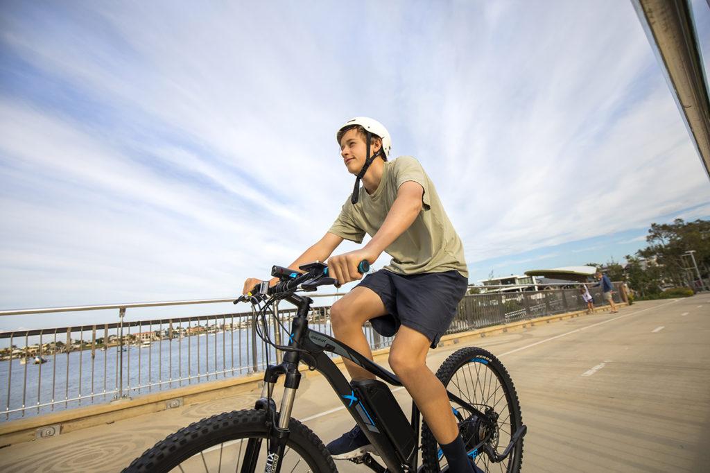Man riding an e-bike on a path next to a canal